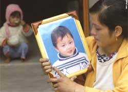 Mother holds portrait of her deceased son