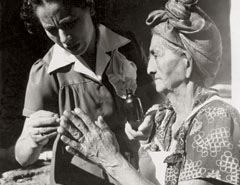 Public health nurse instructs elderly midwife on basic hygiene